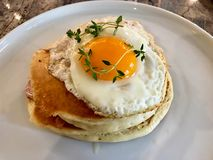 Den saltade pannkakasmörgåsen med Fried Eggs, frasig bacon och timjan lämnar/den salta organiska frukosten arkivfoto
