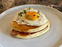 Den saltade pannkakasmörgåsen med Fried Eggs, frasig bacon och timjan lämnar/den salta organiska frukosten royaltyfri fotografi