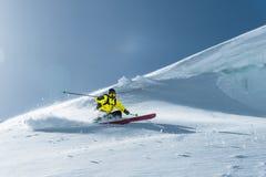 Den sammanlagda längden av skidåkning på nytt snöpulver Yrkesmässig skidåkare utanför spåret på en solig dag royaltyfri fotografi