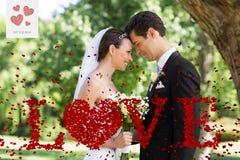 Den sammansatta bilden av att älska nyligen gifta sig par i trädgård Royaltyfri Fotografi