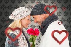 Den sammansatta bilden av att le par i vinter danar att posera med rosor Royaltyfria Bilder