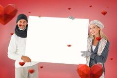Den sammansatta bilden av att le par i vinter danar den hållande affischen Arkivbilder