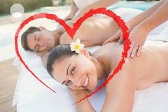 Den sammansatta bilden av attraktiva par som tycker om par, masserar poolsiden Royaltyfria Bilder
