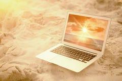 Den sammansatta bilden av bärbara datorn höll på sand på stranden royaltyfria bilder