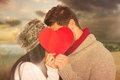 Den sammansatta bilden av barn kopplar ihop att kyssa bak röd hjärta Arkivbilder