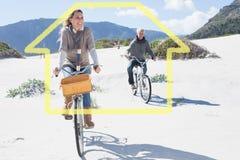 Den sammansatta bilden av bekymmerslösa par som går på en cykel, rider på stranden Royaltyfri Fotografi