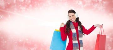 Den sammansatta bilden av brunetten i vinter beklär hållande shoppingpåsar Arkivfoton