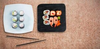 Den sammansatta bilden av den över huvudet sikten av sushi och skaldjur tjänade som i svart platta Arkivbild