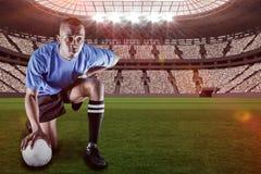 Den sammansatta bilden av den allvarliga rugbyspelaren som knäfaller, medan hållande, klumpa ihop sig med 3d Arkivfoto