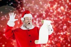Den sammansatta bilden av den förvånade Santa Claus danandeframsidan, medan läs-, bläddrar Fotografering för Bildbyråer