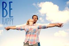 Den sammansatta bilden av den stående yttersidan för lyckliga par med armar sträckte att kyssa Arkivfoton