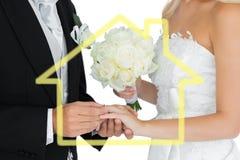 Den sammansatta bilden av den unga brudgummen som sätter på vigselringen på hans wifes, fingrar Arkivfoto