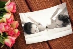 Den sammansatta bilden av fridsamma par som tycker om par, masserar poolsiden Royaltyfri Foto