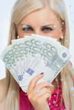 Den sammansatta bilden av gräsplan synade kvinnan som rymmer 100 eurosedlar Royaltyfri Bild