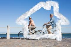 Den sammansatta bilden av lyckliga tillfälliga par som går för en cykel, rider på pir Royaltyfri Bild