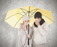 Den sammansatta bilden av par i vinter danar att nysa under paraplyet Royaltyfria Bilder