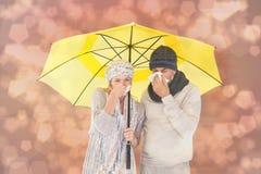 Den sammansatta bilden av par i vinter danar att nysa under paraplyet Arkivbild