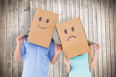 Den sammansatta bilden av par som bär den ledsna framsidan, boxas på deras huvud royaltyfri fotografi