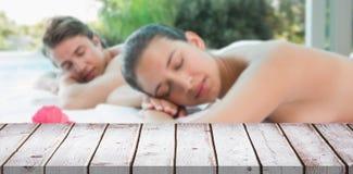 Den sammansatta bilden av par som ligger på massagetabellen på brunnsorten, centrerar Royaltyfri Foto