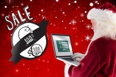 Den sammansatta bilden av Santa Claus använder en bärbar dator Arkivbild
