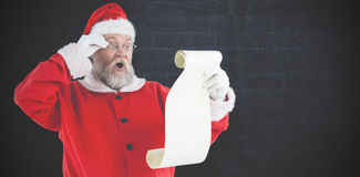 Den sammansatta bilden av Santa Claus danandeansiktsuttryck, medan läs-, bläddrar Fotografering för Bildbyråer