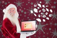 Den sammansatta bilden av Santa Claus framlägger en bärbar dator Arkivfoton