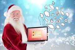 Den sammansatta bilden av Santa Claus framlägger en bärbar dator Royaltyfria Foton