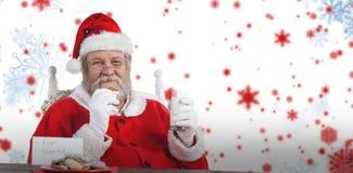 Den sammansatta bilden av Santa Claus hållande exponeringsglas av mjölkar och kakan vid tabellen Royaltyfria Bilder