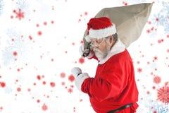 Den sammansatta bilden av Santa Claus som ser armbandsuret, medan hållande, plundrar mycket av julgåvor Fotografering för Bildbyråer