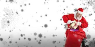 Den sammansatta bilden av Santa Claus som tar bort gåvor från jul, hänger löst Arkivbild