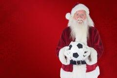 Den sammansatta bilden av santa rymmer en klassisk fotboll Arkivfoto