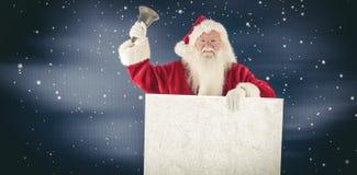 Den sammansatta bilden av santa rymmer ett tecken och ringer hans klocka Royaltyfri Foto