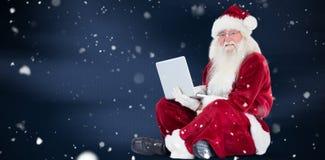 Den sammansatta bilden av santa sitter och använder en bärbar dator Fotografering för Bildbyråer