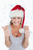 Den sammansatta bilden av ståenden av en kvinna med tummarna up och en julhatt Arkivfoto