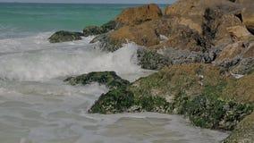 Den sandiga kusten för havet med färgstänk av vågor på vaggar lager videofilmer