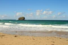 Den sandiga stranden med högväxt vaggar Arkivfoto