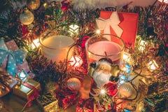 Den Santa Claus hållklockan och vit och Violet Candle, prydnaden och jul dekorerar för natt för glad jul och lyckligt nytt år Fotografering för Bildbyråer