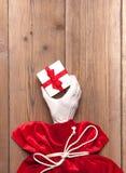 Den Santa Claus handen ger en gåva från den röda påsen på gammal träbakgrund Royaltyfri Foto