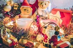 Den Santa Claus hållklockan och jul undersöker, kopplar ihop nallebjörnar, och prydnaden dekorerar glad jul, lyckligt nytt år Arkivfoto