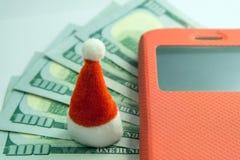 Den Santa Claus souvenirhatten står på bakgrunden av femhundra US dollar bredvid en mobiltelefon i ett rött fall Begreppet av arkivfoton