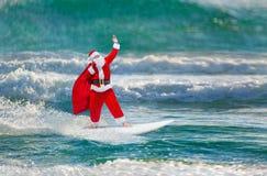 Den Santa Claus surfaren med gåvor plundrar att surfa på havvågor Fotografering för Bildbyråer