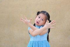 Den Sassy lilla asiatiska ungeflickan med den roliga framsidan och uttryckt korsar ens arm arkivbilder