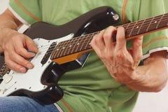 Den satta gitarristen fingrar för ackord på slut för elektrisk gitarr upp royaltyfri foto