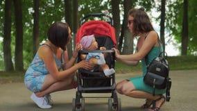 Den satta modern och hennes vän och roar barnet i sittvagnen arkivfilmer