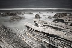 Den sceniska atlantiska kustlinjen med vågor i rörelse vaggar omkring på den sandiga stranden i lång exponering, bidart, det basq royaltyfria bilder