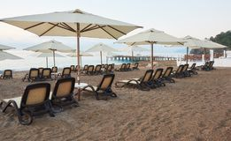 Den sceniska sikten av den privata sandiga stranden med solen bäddar ned från havet och bergen Amara Dols Vita Luxury Hotel semes Fotografering för Bildbyråer