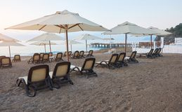 Den sceniska sikten av den privata sandiga stranden med solen bäddar ned från havet och bergen Amara Dols Vita Luxury Hotel semes Royaltyfri Bild