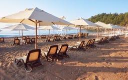 Den sceniska sikten av den privata sandiga stranden med solen bäddar ned från havet och bergen Amara Dols Vita Luxury Hotel semes Arkivbild