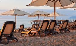 Den sceniska sikten av den privata sandiga stranden på stranden med solen bäddar ned mot havet och bergen Amara Dolce Vita Luxury Arkivbild