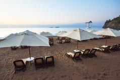 Den sceniska sikten av den privata sandiga stranden på stranden med solen bäddar ned mot havet och bergen Amara Dolce Vita Luxury Royaltyfri Foto
